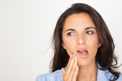 Image of a woman holding her jaw in pain. Learn more about scaling and root planing at River's Edge Dental in Great Falls, MT